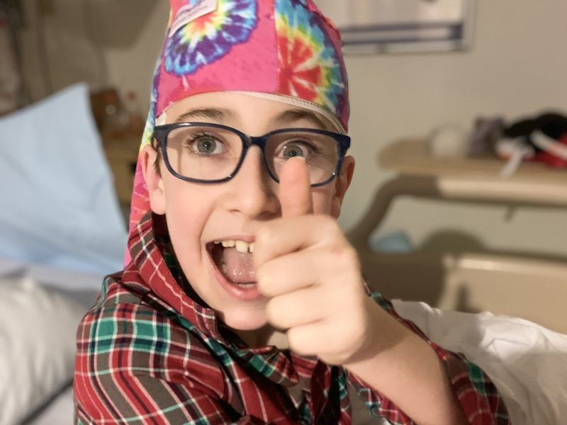 boy giving thumbs up during eeg while wearing a tie dye nillynoggin eeg cap