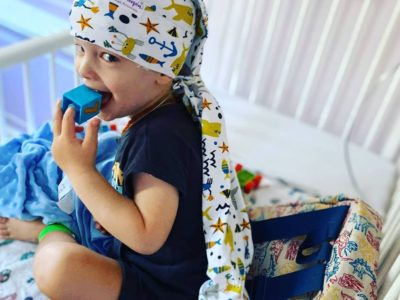 boy putting blue block to his mouth during eeg while wearing the shark nillynoggin eeg cap
